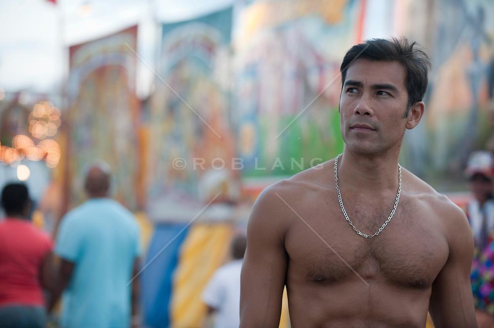 Shirtless Asian American man at a carnival