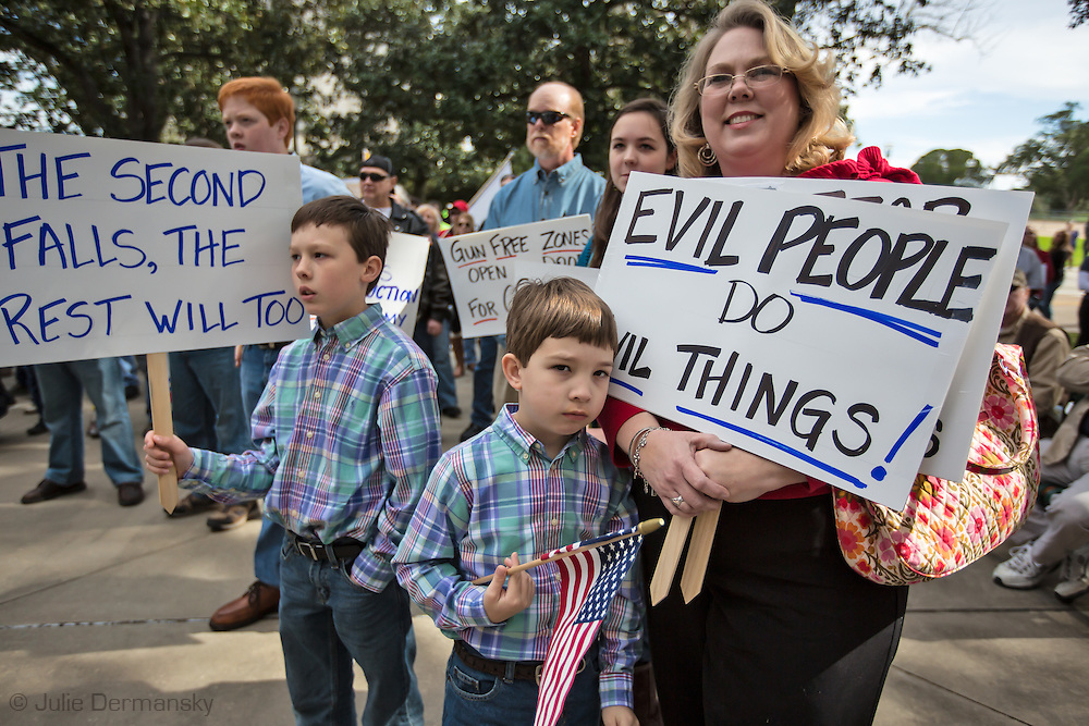 "January 18, Baton Rouge , Fran McConnelle with her sons, 6 year old  Turner  and  9 year old Rex at a pro-gun rally organized by ""Guns across America"" on ""Gun Appreciation Day"" with anti Democratic policical signs. After the massacre at  a school in Sandy Hook, Connecticut , the debate over gun control in America became a key political issue."