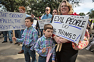 """January 18, Baton Rouge , Fran McConnelle with her sons, 6 year old  Turner  and  9 year old Rex at a pro-gun rally organized by """"Guns across America"""" on """"Gun Appreciation Day"""" with anti Democratic policical signs. After the massacre at  a school in Sandy Hook, Connecticut , the debate over gun control in America became a key political issue."""