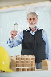 Architect with champagne glass and architectural model