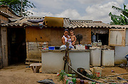 Mrs. Sâmila holds his son, Isaías Felipe, while she cleans some kitchen utensils in a makeshift sink outside her shack at Vitória Occupancy, Isidoro region.
