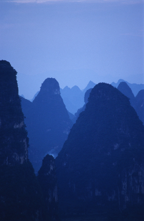 Tinged with blue the Karst peaks stand silhouetted in the Yangshuo and Guilin landscape of Guanxi Province.