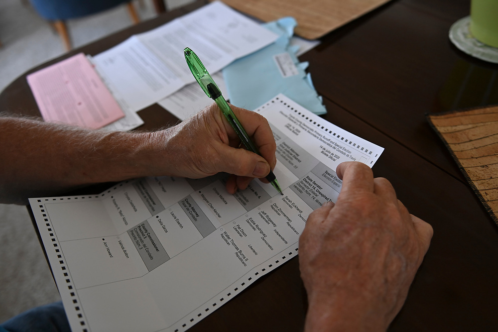 Austin, Texas USA July 7, 2020: A voter fills out the mail-in Democratic runoff ballot for a summer election delayed in Texas by the coronavirus pandemic.  Accusations of voter fraud through mail in ballots continue to be raised but are not supported by evidence with the Secretary of State.