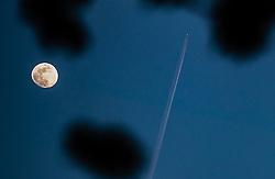 THEMENBILD - ein Flugzeug hinterlässt Kondensstreifen am Himmel bei Sonnenuntergang neben dem Vollmond, aufgenommen am 27. April 2018 in Zell am See, Österreich // An airplane leaves a contrail as it passes the Moon over Zell am See, Austria on 2018/04/27. EXPA Pictures © 2018, PhotoCredit: EXPA/ JFK