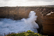 A large wave crashes against the coastline at the entrance to Loch Ard Gorge, located on the Great Ocean Road in Victoria, Australia