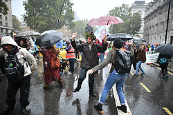 © Licensed to London News Pictures. 08/10/2019. London, UK. Extinction Rebellion activists dancing in the rain on Whitehall, outside Downing Street. Activists have converged on Westminster for a second day, blockading roads in the area and calling on government departments to 'Tell the Truth' about what they are doing to tackle the Emergency. Photo credit: Ben Cawthra/LNP