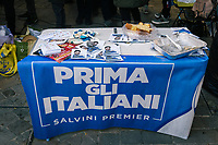 "CESENATICO, ITALY - 5 JANUARY 2020: A table with a ""Italians First"" flag, candidate flyer, League balloons and food is seen here during a rally with Matteo Salvini, former Interior Minister of Italy and leader of the far-right League party,  in Cesenatico, Italy, on January 5th 2020.<br /> <br /> Matteo Salvini is campaigning in the region of Emilia Romagna to support the League candidate Lucia Borgonzoni running for governor.<br /> <br /> After being ousted from government in September 2019, Matteo Salvini has made it a priority to campaign in all the Italian regions undergoing regional elections to demonstrate that, in power or not, he still commands considerable support.<br /> <br /> The January 26th regional elections in Emilia Romagna, traditionally the home of the Italian left, has been targeted by Matteo Salvini as a catalyst for bringing down the government. A loss for the center-left Democratic Party (PD) against Mr Salvini's right would strip the centre-left party of control of its symbolic heartland, and probably trigger a crisis in its coalition with the Five Star Movement."