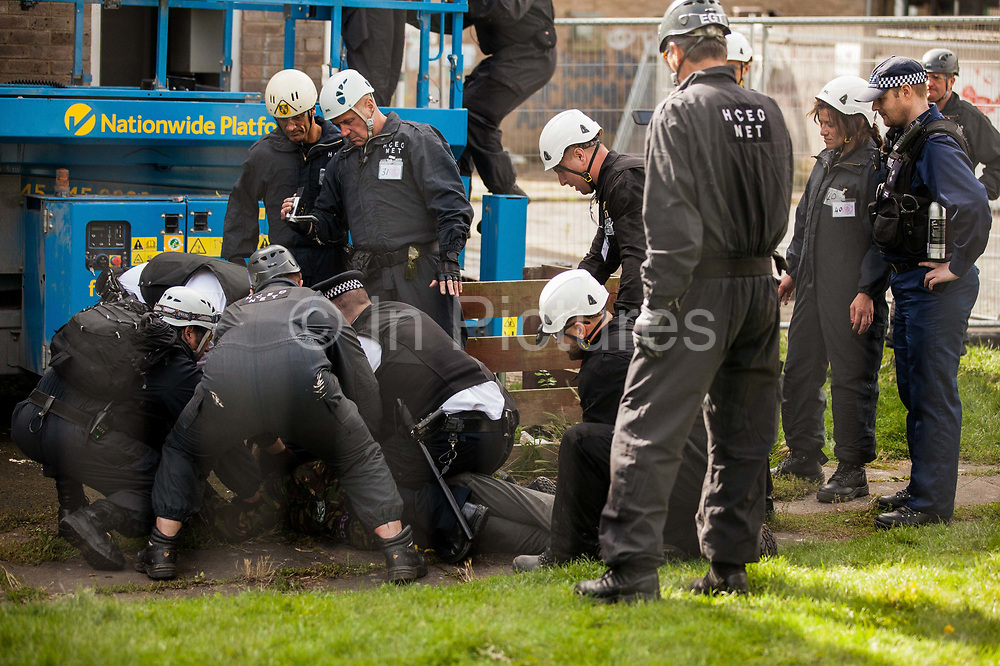 Bailiffs and police officers retrieve a housing activist from a cherry picker used for evictions from the Sweets Way housing estate on 23rd September 2015 in London, United Kingdom. A group of housing activists calling for better social housing provision in London had occupied some of the properties on the 142-home estate in Whetstone, in some cases refurbishing properties intentionally destroyed by the legal owners following eviction of the original residents, in order to try to prevent the eviction of the last resident on the estate and the planned demolition and redevelopment of the entire estate by Barnet Council and Annington Property Ltd.