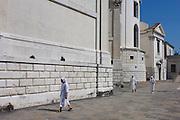 Three nuns walk in afternoon heat under the walls of Santa Maria della Salute church in Dorsoduro, a district of Venice, Italy.
