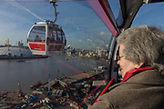 A lady passenger rides in a gondola on a journey over the River Thames on the Emirates Cable Car, from Royal Docks towards the Greenwich Peninsular. There are 34 gondolas, each with a maximum capacity of 10 passengers. The Emirates Air Line (also known as the Thames cable car) is a cable car link across the River Thames in London built with sponsorship from the airline Emirates. The service opened on 28 June 2012 and is operated by Transport for London. The service, announced in July 2010 and estimated to cost £60 million, comprises a 1-kilometre (0.62 mi) gondola line that crosses the Thames from the Greenwich Peninsula to the Royal Docks.