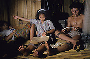 1989: Penan family in sulap. Kayan and his family repairing fishing nets. Long Tedang, Limbang district, Sarawak, Borneo <br /> <br /> Tropical rainforest and one of the world's richest, oldest eco-systems, flora and fauna, under threat from development, logging and deforestation. Home to indigenous Dayak native tribal peoples, farming by slash and burn cultivation, fishing and hunting wild boar. Home to the Penan, traditional nomadic hunter-gatherers, of whom only one thousand survive, eating roots, and hunting wild animals with blowpipes. Animists, Christians, they still practice traditional medicine from herbs and plants. Native people have mounted protests and blockades against logging concessions, many have been arrested and imprisoned.