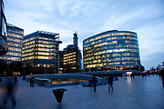 Dusk falls over More London business district. As the office buildings become lighter than outside, the blue hour passes into early evening.