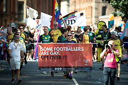 """© Licensed to London News Pictures . 24/08/2019. Manchester, UK. """" Some Footballers are gay get over it """" banner . The 2019 Manchester Gay Pride parade through the city centre , with a Space and Science Fiction theme . Manchester's Gay Pride festival , which is the largest of its type in Europe , celebrates LGBTQ+ life . Photo credit: Joel Goodman/LNP"""