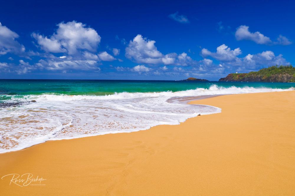 Surf and sand on Secret Beach (Kauapea Beach), Kilauea Lighthouse visible, Island of Kauai, Hawaii
