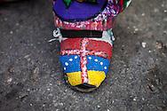 """Detalle del calzado de El Diablo Mayor, Roberto """"Robin"""" Izaguirre, durante la festividad del Corpus Christi, representada en Venezuela a traves del ritual magico-religioso de los Diablos Danzantes. Los Diablos de Naiguata se identifican por pintar sus propios trajes y decorarlos con cruces, rayas y circulos, figuras que impiden que el maligno los domine. Las mascaras son en su gran mayoria animales marinos. Llevan escapularios cruzados, crucifijos y cruces de palma bendita. Naiguata, 30 Mayo 2013. (ivan gonzalez)"""