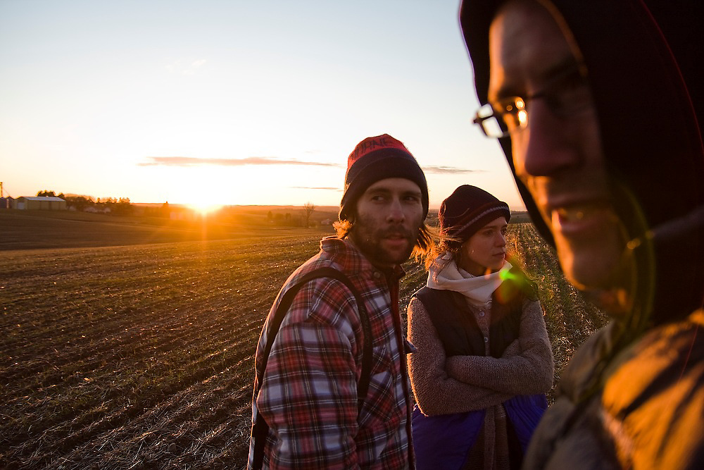 Three friends stand in a field at sunset in the Palouse Valley near Spokane, Washington.