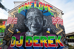 """© Licensed to London News Pictures; 11/08/2021; Bristol, UK. A giant mural of DJ Derek is seen on the side of a house by Junction 2 of the M32 motorway which will be passed by 150,000 vehicles a month. Two of the world's most famous street artists are among the team working on the tribute together, Bristol-based Harriet Wood, aka Hazard One has painted the image of DJ Derek, and Inkie is putting the finishing touches to the words and framing around the giant portrait. The project to create a lasting mural to DJ Derek began last year after a previous mural was tagged, and then painted over, to the dismay of family and friends. Artists, music fans and Derek's family came together with a fundraising campaign, that was then boosted by Arts Council backing. DJ Derek was born Derek Serpell-Morris (18 December 1941 – July 2015) and was an English DJ based in Bristol. In a DJ career that spanned over 40 years, he was known for playing a blend of 60s rocksteady, reggae, ska, dancehall and soul. He was reported missing in July 2015 and his remains were found near Cribbs Causeway on 10 March 2016 but police said they were not treating his death as suspicious. A former accountant at Cadburys, Derek began his DJ career in his mid-30s. He said he finished most sets with the Bob Marley hit """"One Love"""", saying it's a perfect signing-off record for a reggae set—let's get together and feel all right. He MCed in Jamaican Patois while DJing. Photo credit: Simon Chapman/LNP."""