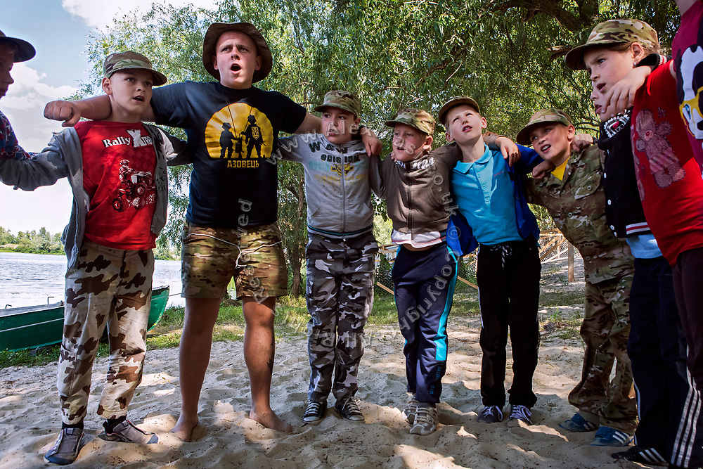 An instructor at the ultra-nationalistic Azovets children's camp is bonding with participants after martial arts training, on the banks of the Dnieper river, in Kiev, Ukraine's capital.
