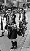 Członkowie zespołu folklorystycznego niosą kontrabas zmierzając na występ. Kraków, koniec lat 80. XX wieku.