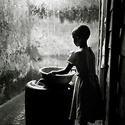 A housegirl collects rain water inside the counselor Mama Jeannette's house who hired other victims and orphans to do various housework.