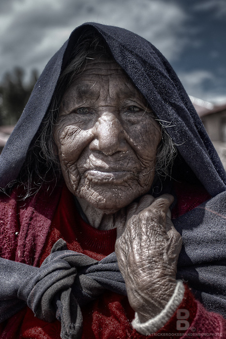 A close up portait of an elderly Quecha women on Taquile Island of Lake Titicaca showing her aged through sharp detail and contrast in a smooth tone.
