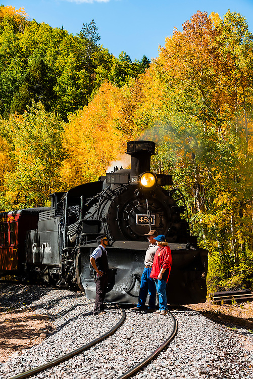 A brakeman talks with several passengers during a brief stop near Calico, CO, surrounded by a grove of aspen trees in peak autumn color on the Cumbres & Toltec Scenic Railroad train on the 64 mile run between Chama, New Mexico and Antonito, Colorado. The railroad is the highest and longest narrow gauge steam railroad in the United States with a track length of 64 miles. The train traverses the border between Colorado and New Mexico, crossing back and forth between the two states 11 times. The narrow gauge track is 3 feet wide. It runs over 10,015 ft (3,053 m) Cumbres Pass.