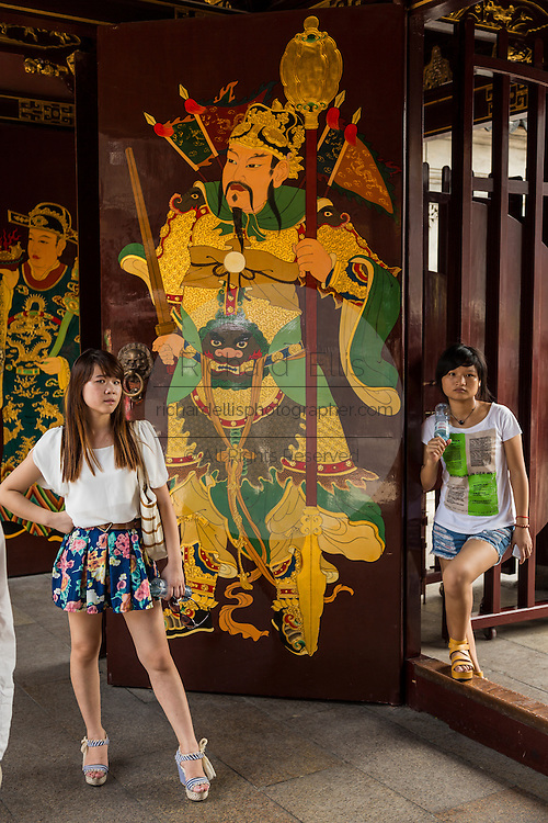 A young fashionable woman stands at the gate of Chenghuang Miao or City God Temple in Yu Yuan Gardens bazaar Shanghai, China