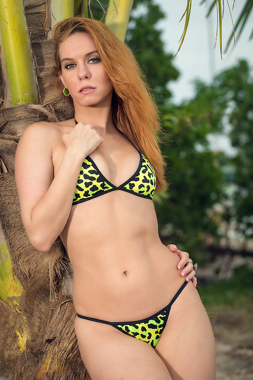 Young woman in a tropical beach wearing a bikini and looking at camera in sensual pose while resting on a palm tree.