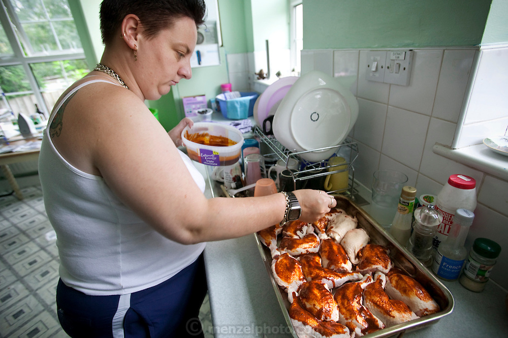 """Jill McTighe, a mother and school aide, bastes chicken for Sunday dinner in her kitchen in Willesden, London, United Kingdom. (Jill McTighe is featured in the book What I Eat: Around the World in 80 Diets.)  The caloric value of her day's worth of food on a """"bingeing"""" day in the month of September was 12300 kcals. The calorie total is not a daily caloric average.  Jill is 31 years old; 5 feet, 5 inches tall;  and 230 pounds. Honest about her food addiction replacing a drug habit, Jill joked about being a chocoholic as she enthusiastically downed a piece of chocolate cake at the end of the photo session. Her weight has yo-yoed over the years and at the time of the picture she was near her heaviest; walking her children to school every day was the sole reason she didn't weigh more. She says this photo experience was a catalyst for beginning a healthier diet for herself and her family.  MODEL RELEASED. [Use of Jill McTighe images must be used contextually only and use cleared with Peter Menzel Photography on a case by case basis.]"""