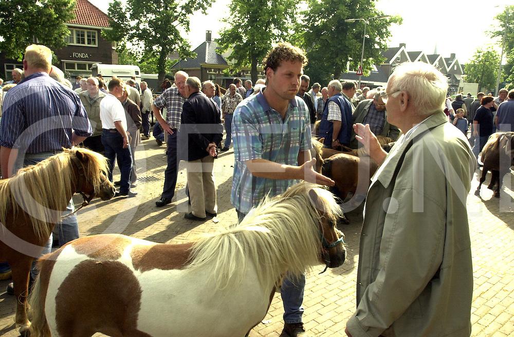 fotografie frank uijlenbroek©2001 frank uijlenbroek.010710 ommen ned.Het eeuwenoude feest Ommer Bissingh is ook dit jaar weer gestart op de tweede dinsdag van juli. De Bissingh sinds 1567 gehouden kenmerkte zich door o.a. een jaarmarkt en veemarkt. Beide zijn behouden gebleven al is de veemakrt meer in een paarden en ponymarkt verandert en is de jaarmarkt een toeristische atractie geworden..foto : handel s'morgens om 09.00 uur.