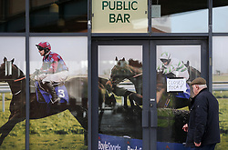A racegoer attempts to enter a bar at the track despite a 'Closed Today' sign during the rescheduled Easter Tuesday Meeting at Fairyhouse, Ratoath.