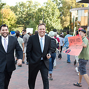 2 men in suits walk past a group of Occupy CLT protestors on the way back from a demonstration in front of Bank Of American HQ in uptown Charlotte.