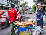 """04 OCTOBER 2012 - BANGKOK, THAILAND: A vendor who sells fried snacks like dough balls and banana fritters, works on Sukhmvit Soi 22 in central Bangkok.  Thailand in general, and Bangkok in particular, has a vibrant tradition of street food and """"eating on the run."""" In recent years, Bangkok's street food has become something of an international landmark and is being written about in glossy travel magazines and in the pages of the New York Times.       PHOTO BY JACK KURTZ"""