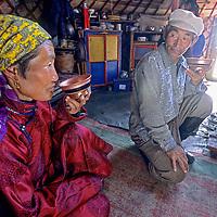 MONGOLIA, Battogtokh (L) & her husband Dorjgoo enjoy salty tea during a break from making felt in Darhad Valley.
