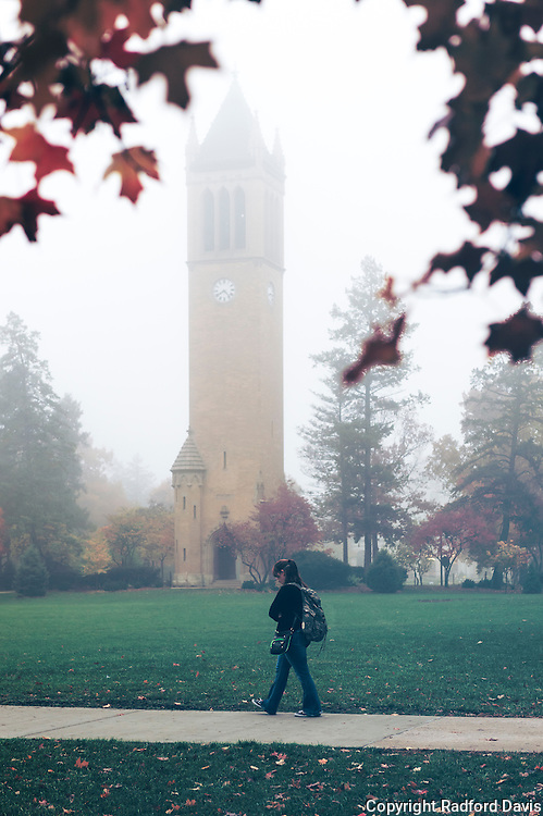 Iowa State University in the autumn. A students walks past the campanile.