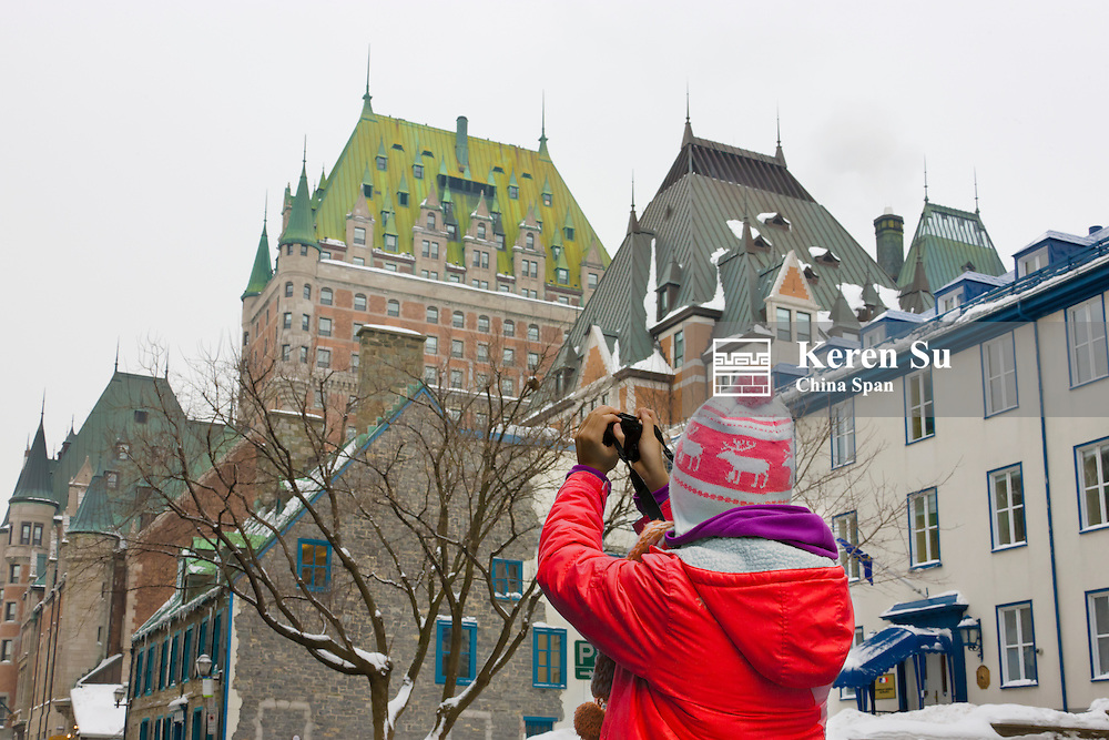Girl photographing Fairmont Le Chateau Frontenac, Quebec City, Canada