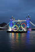 London, UK. Friday 27th July 2012. Olympic flame about to pass Tower Bridge with and the Olympic rings on way to the opening ceremony. London's greatest landmark bridge lights up as the Olympic torch passes by in a high speed boat.