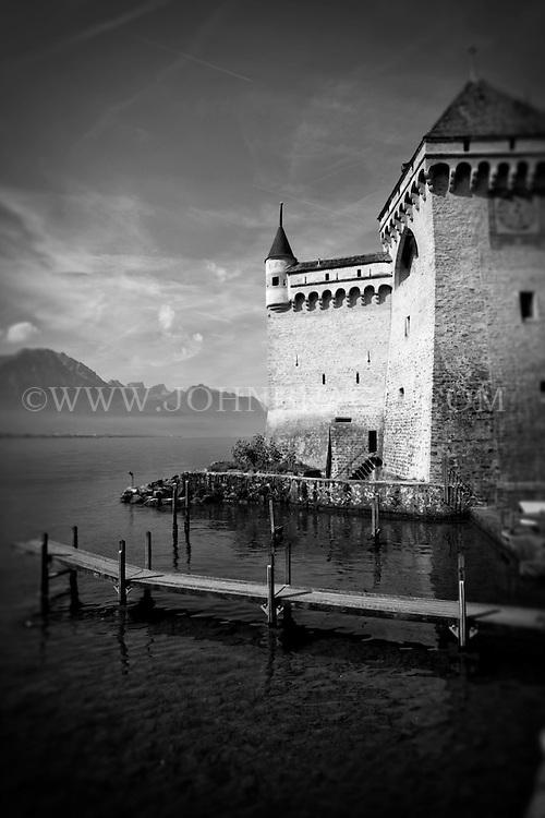 Black and white scenic photo of the Chateau de Chillon and Lake Geneva in Montreux, Switzerland.