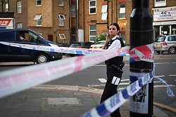 © Licensed to London News Pictures. 01/07/2019. London, UK.  A police officer stands over crime scene ahead of forensics. A man is fighting for his life in hospital having sustained puncture injuries to the neck by what appeared to a a broken wine bottle. The victim in his 30s is understood to be in a critical condition following the assault. Police responded to a call at 5.12pm reporting a fight and attended an address in Argyle Road, West Ealing. Another man also in his 30s has been arrested.Photo credit: Guilhem Baker/LNP