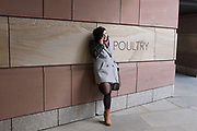 Young woman on her mobile phone leaning against a sign for a building along Poultry in the City of London, UK.