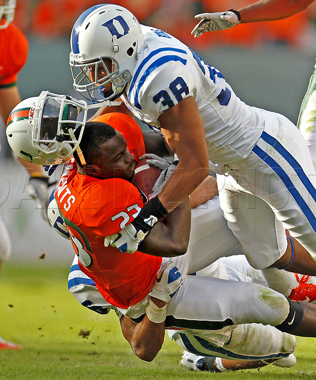 Miami's Eduardo Clement's helmet pops off just short of a touchdown as he is stopped by Duke's Jordon Byas in the third quarter during the University Miami vs Duke game at Sun Life Stadium in Miami Gardens on Saturday,