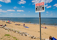 Sands Point, New York, U.S. - July 5, 2014 - A looming warning sign cautions visitors not to climb or walk on the seawall on the shoreline of Sands Point Preserve, on the Long Island Sound Gold Coast. The North Shore public beach had many visitors this Saturday of the long Independence Day holiday weekend when sunny warm weather arrived after the rainy July 4th.