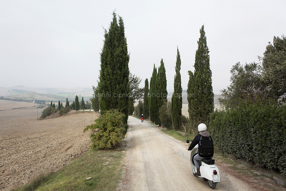 Asciano, Italy - 10 September 2014: Journalist Tina Nachtmann rides a Vespa 125 Primavera of 1974 on a road trip through Tuscany , through the Crete Senesi in Asciano, Italy, on September 10th 2014.<br /> <br /> The Crete Senesi refers to an area of the Italian region of Tuscany to the south of Siena. It consists of a range of hills and woods among villages and includes the comuni of Asciano, Buonconvento, Monteroni d'Arbia, Rapolano Terme and San Giovanni d'Asso, all within the province of Siena. Crete senesi are literally 'Senese clays', and the distinctive grey colouration of the soil gives the landscape an appearance often described as lunar.