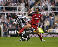 Photo. Glyn Thomas<br />Newcastle United v Bolton Wanderers. <br />Barclaycard Premiership.<br />St James' Park, Newcastle. 20/09/2003.<br />Bolton's Youri Djorkaeff (R) is held back from making a challenge on Titus Bramble.