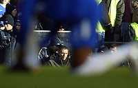26/12/2004 - FA Barclays Premiership - Chelsea v Aston Villa - Stamford Bridge<br />Between the legs of one of his players, tying his shoelaces, Chelsea coach Jose Mourinho sits in the low winter sunshine on the bench.<br />Photo:Jed Leicester/Back Page Images