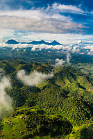 Aerial view of Mt. Muhabura, Mt. Gahingqa and Mt. Sabyinyo in the Virunga Mountains in the background. The Virunga Mountains are a chain of volcanoes in East Africa, along the northern border of Rwanda, the Democratic Republic of the Congo and Uganda. The mountain range is a branch of the Albertine Rift Mountains, which border the western branch of the East African Rift. They are located between Lake Edward and Lake Kivu.