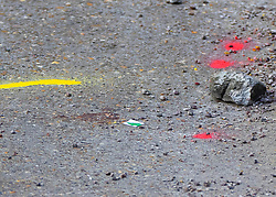 © Licensed to London News Pictures. 23/04/2021. Walton-on-Thames, UK. A police evidence marker points to a blood stain in the car park of a Marks and Spencer store in Walton-on-Thames after a man was killed in an altercation. Police were called to Church Street around 2.15pm on 22/04/2021 following reports that an altercation had taken place between a group of men. One of the men then got into his car, a white 1 series BMW, and is reported to have driven at two of the other men in the group.  One man was killed and another injured. The driver of the car has been arrested on suspicion of murder and attempted murder. Photo credit: Peter Macdiarmid/LNP