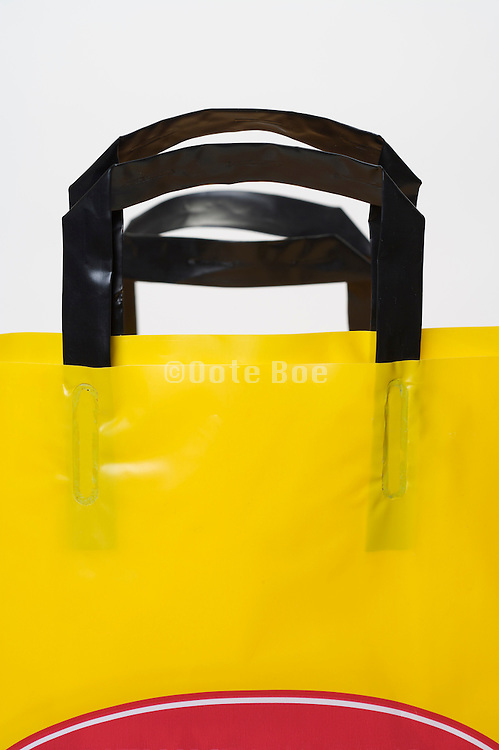 handles of two sturdy plastic shopping bags placed in each other