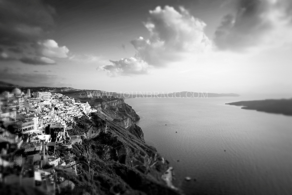 Black and white photo of a cliffside in Santorini, Greece at sunset.