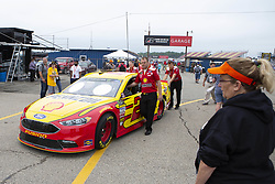 June 10, 2018 - Brooklyn, Michigan, U.S - Crew members of the Shell Pennzoil Ford driven by JOEY LOGANO (22) push his car through the garage area at Michigan International Speedway. (Credit Image: © Scott Mapes via ZUMA Wire)